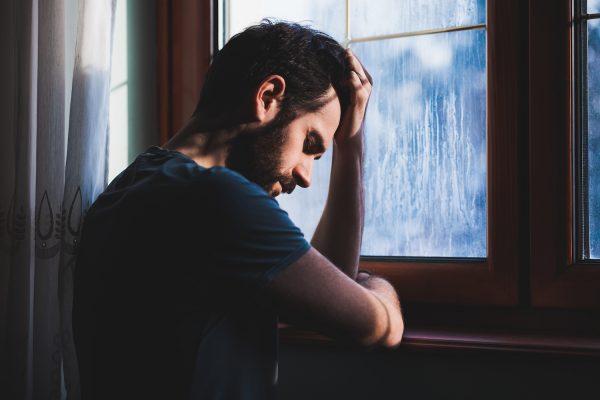 Мужчина грустит около окна