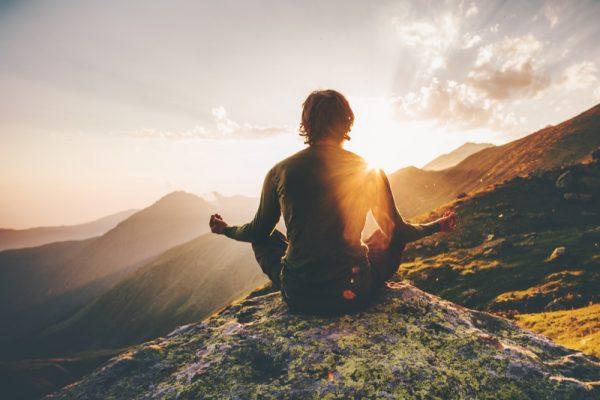 Мужчина медитирует на вершине склона