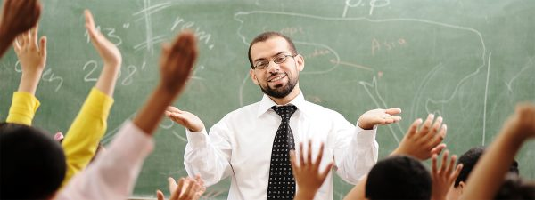 Мужчина на фоне доски и поднятых рук учеников