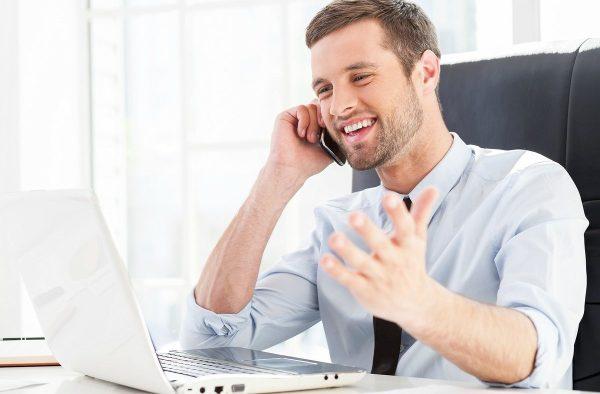 Мужчина разговаривает по телефону и смеётся