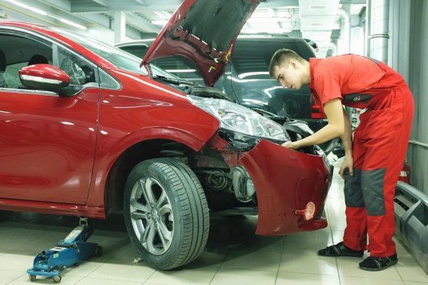 Мужчина ремонтирует авто