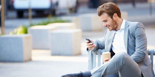 Мужчина с кофе и телефоном сидит на улице