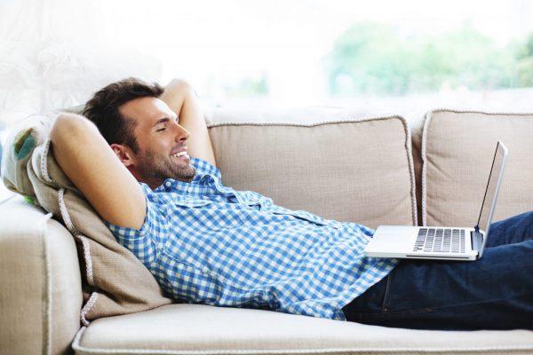 Мужчина с ноутбуком на диване