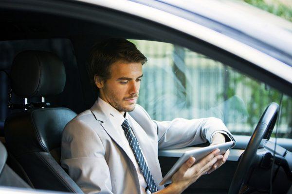 Мужчина с планшетом в автомобиле
