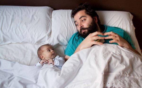 Мужчина с ребёнком лежат в кровати