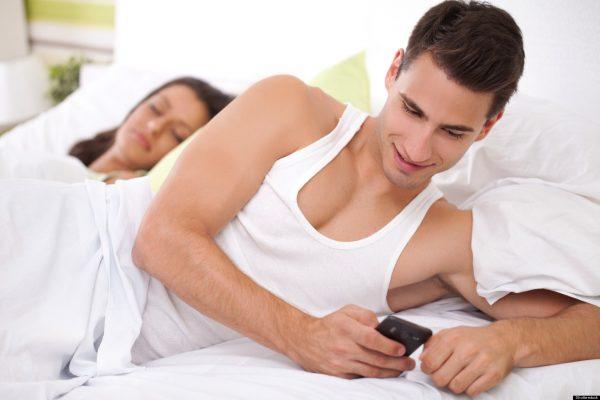 Мужчина с телефоном лежит в кровати