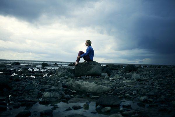 Мужчина сидит на камне около воды