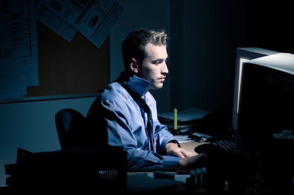 Мужчина сидит за компьютером ночью
