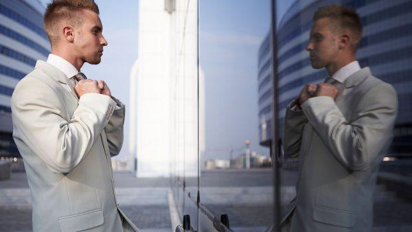 Мужчина смотрит на своё отражение