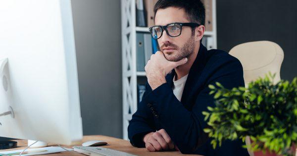 Мужчина в очках за столом