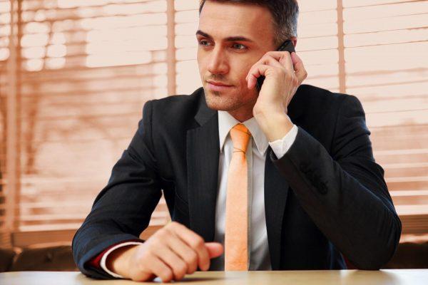 Мужчина в пиджаке разговаривает по телефону