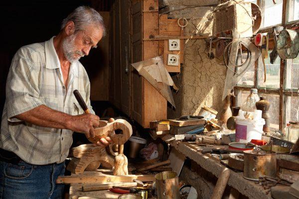 Мужчина вырезает фигуры из дерева