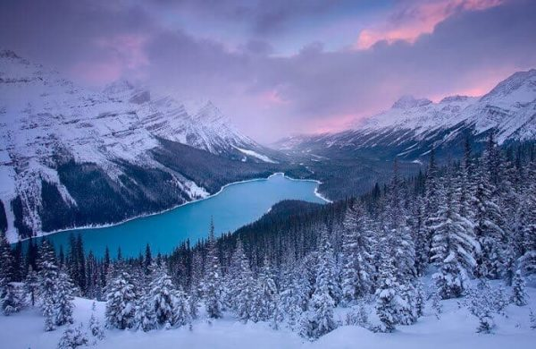 Озеро среди гор и зимнего леса