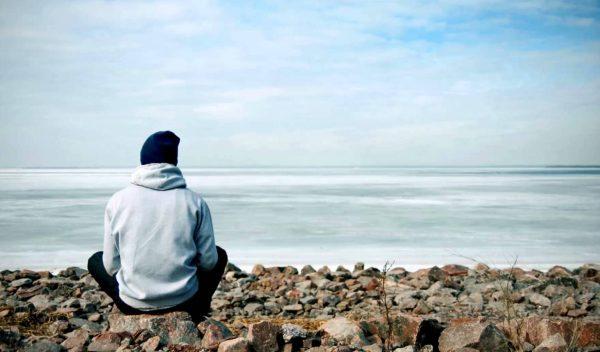 Парень сидит на берегу