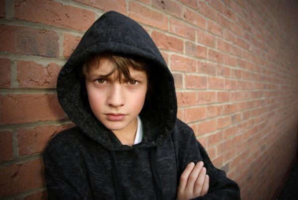 Подросток у кирпичной стены