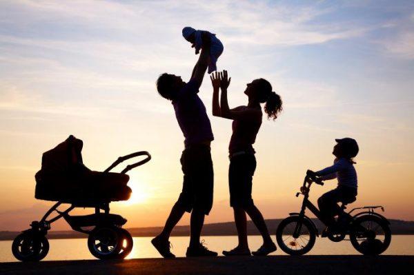 Счастливая семья на фоне заходящего солнца