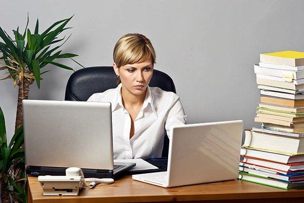 Строгая женщина работает за ноутбуком