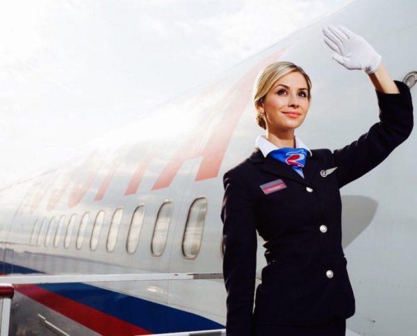 Стюардесса возле самолёта машет рукой