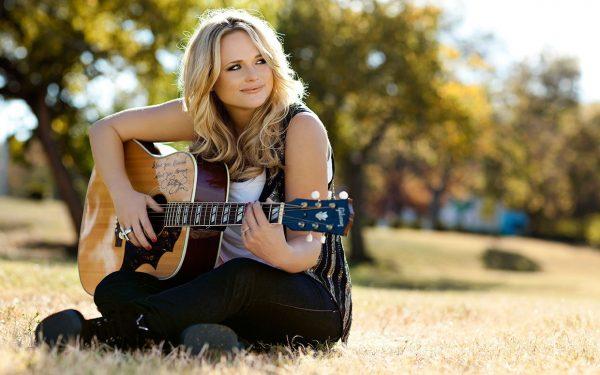 Девушка сидит на поляне и играет на гитаре