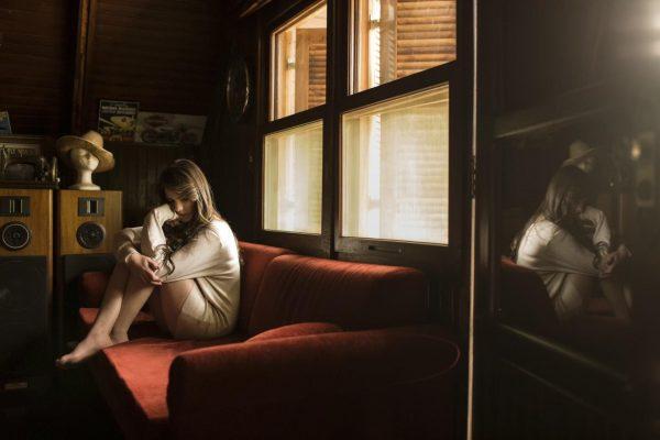 Задумчивая девушка сидит на диване