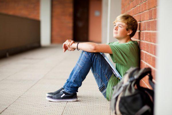Задумчивый юноша сидит у стены