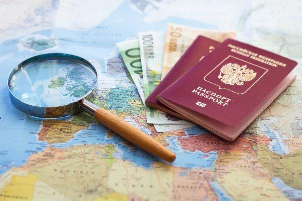 Загранпаспорт, деньги и лупа на карте