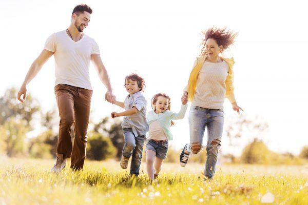 Жена, муж и дети бегут по траве