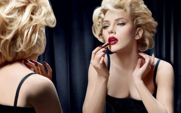 Женщина красит губы