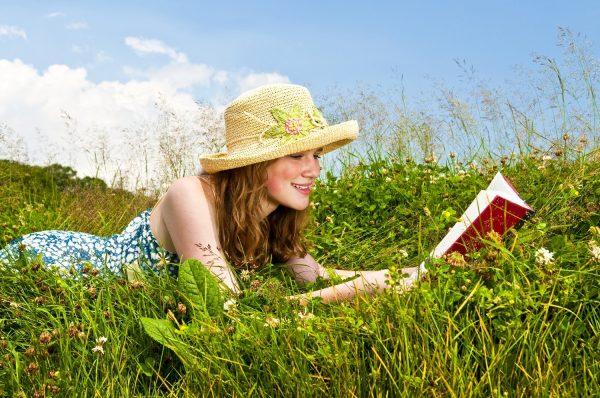 Девушка читает книгу на природе