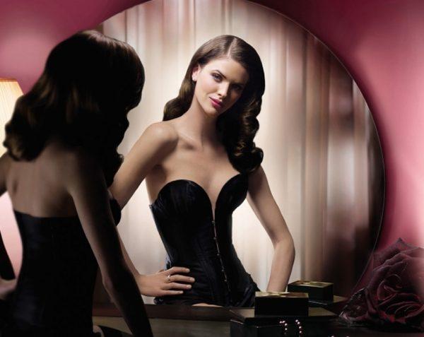 Девушка любуется на своё отражение в зеркале