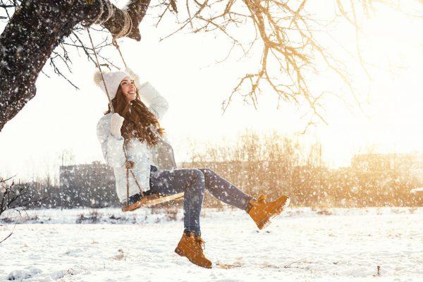Девушка зимой катается на качелях