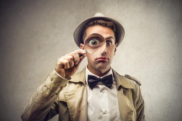 Фото мужчины в щегольском наряде с лупой перед глазами