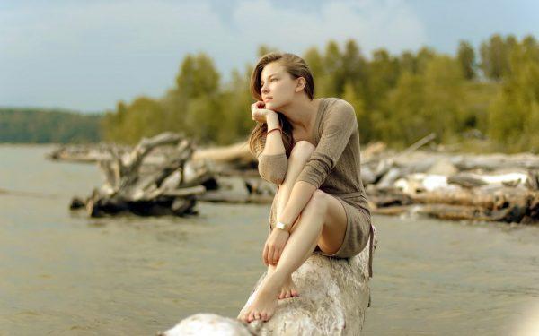 Девушка сидит на берегу и размышляет
