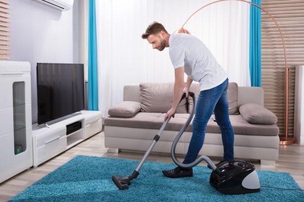Мужчина пылесосит ковёр