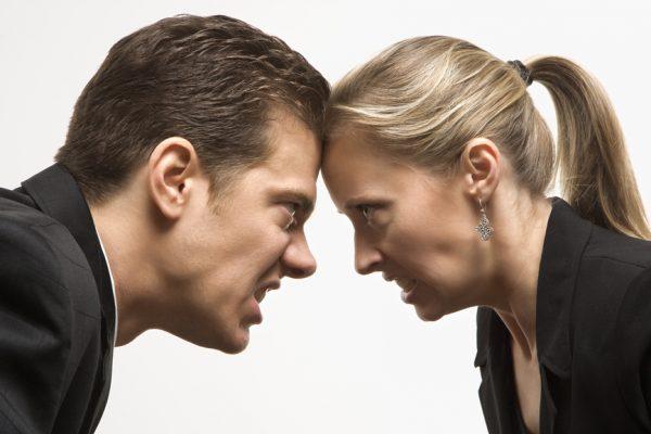 Мужчина и женщина смотрят друг на друга со злобой
