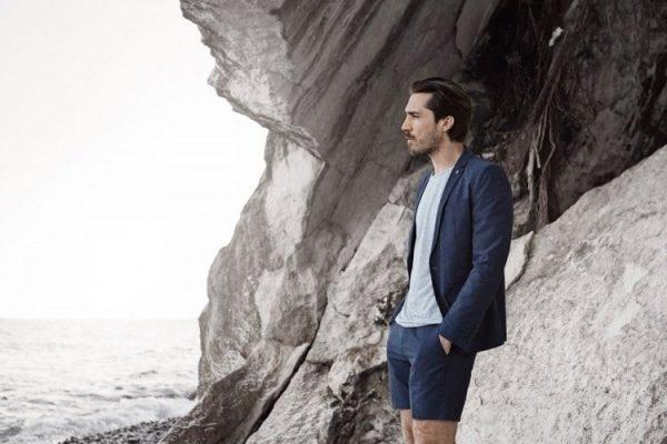 Мужчина на фоне скалы смотрит на море