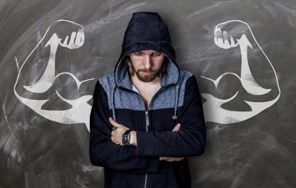 Мужчина с бородой на фоне меловой доски с нарисованными руками