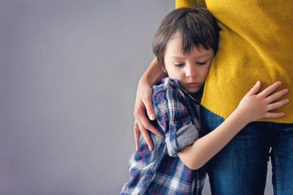 Обидчивый мальчик держится за маму