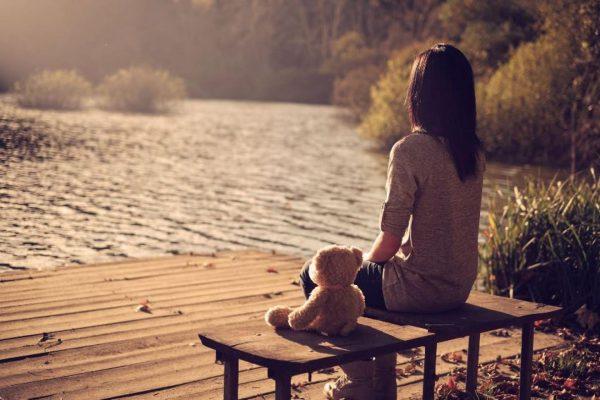 Девушка сидит в одиночестве на берегу