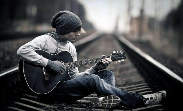 Парень с гитарой на железнодорожных путях