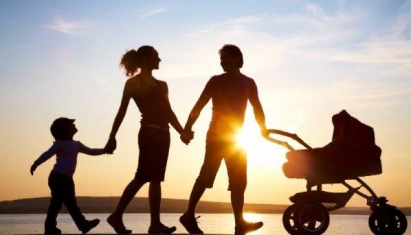 Семья прогуливается у моря на закате