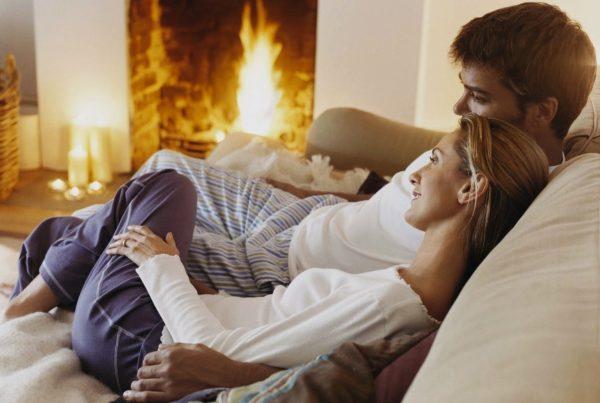 Мужчина и женщина уютно сидят у камина