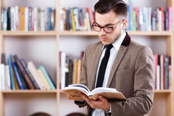 Мужчина в очках читает книгу