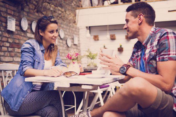 Парень и девушка разговаривают за столом